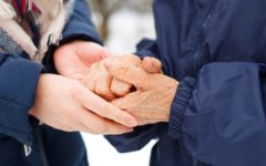 Close up picture of a woman holding her grandmother's aged hands Shutterstock